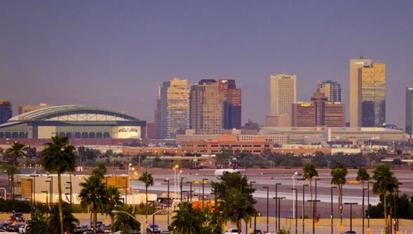 The Phoenix skyline glimmers at sunrise, as seen from
