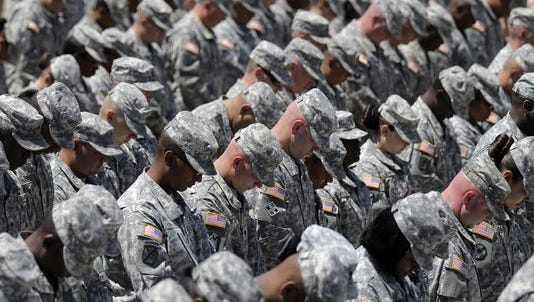 Soldiers bow their heads during a memorial ceremony for shooting victims, Wednesday, April 9, 2014, at Fort Hood, Texas.