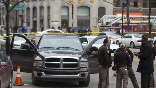 Law enforcement personnel investigate a shooting scene in front of the City-County Building, Indianapolis, Wednesday, Feb. 11, 2015. At least one person was transported to a local hospital.