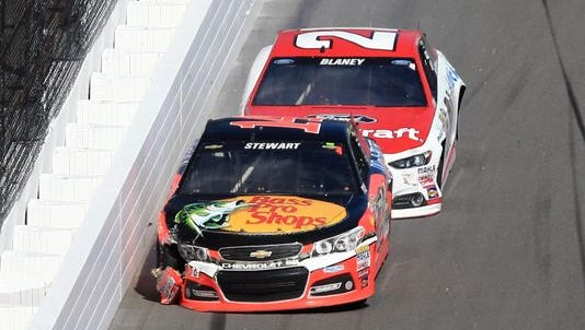 Tony Stewart (14) hits the wall in front of Ryan Blaney (21) during the Daytona 500.