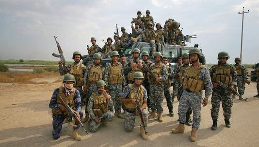 In this Oct. 27, 2014, file photo, Iraqi federal policemen pose for a photograph as they arrive to join the fighting against the Islamic State group in Jurf al-Sakhar, 43 miles south of Baghdad, Iraq.