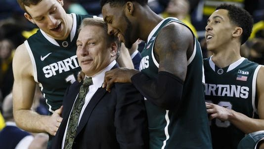 Michigan State Spartans head coach Tom Izzo (center), forward Matt Costello (left), guard/forward Branden Dawson (22), and guard Travis Trice.