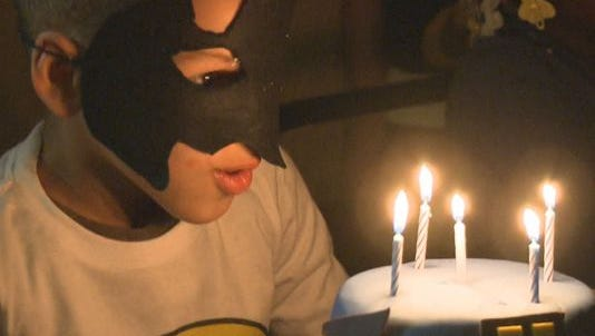 Four-year-old Ashton blows out candles to his very own birthday cake.