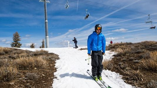 A skier threads his way through patches of dry ground last month at Squaw Valley.