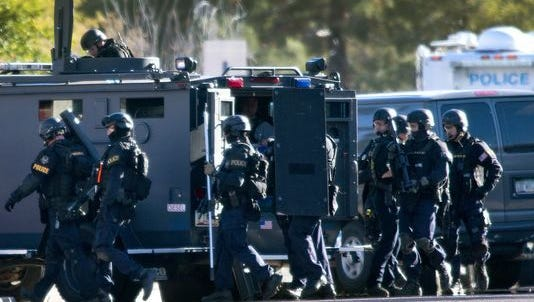 A Phoenix SWAT team enters a house at 28th St. and Acoma in 2013 in search of the gunman who opened fire in an office building at 16th St. and Glendale. Law-enforcement agencies in all 15 Arizona counties have -obtained surplus gear from the Pentagon's 1033 program, as ¬allowed under the National ¬Defense Authorization Act of 1997.