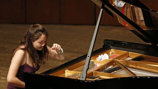 Competitors are competing in a tennis tournament-like bracket in the Cincinnati World Piano Competition. Hanqing Chang, of China, plays during the 2014 World Piano Competition, held in the Corbett Auditorium at University of Cincinnati's College Conservatory of Music.