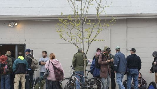 People wait outside the Fort Collins Rescue Mission while an evening meal is being served Monday, April 27, 2015, in Fort Collins, CO.