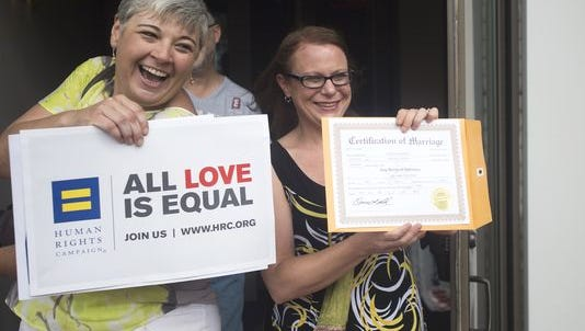 Jessica Dent, left, and Carolee Taylor, right, show their marriage license at the Montgomery County Courthouse on Friday, June 26, 2015 in Montgomery, Ala. Gay and lesbian Americans have the same right to marry as any other couples, the Supreme Court declared Friday in a historic ruling deciding one of the nation's most contentious and emotional legal questions. Celebrations and joyful weddings quickly followed in states, including Alabama, where they had been forbidden.