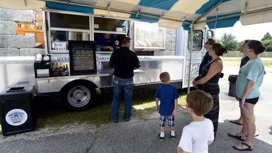 Customers line up for lunch at the Hip Pocket food truck on Barrancas Avenue on Tuesday over the lunch hour. Pensacola City Council is voting Tuesday on whether or not to allow food trucks in the downtown area.