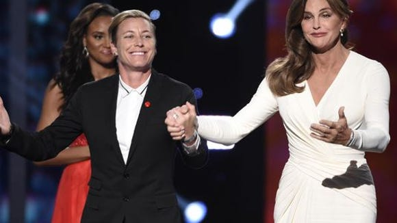 Abby Wambach, left, takes a bow with Caitlyn Jenner after presenting Jenner as the Arthur Ashe Courage Award winner at the ESPYs.