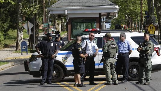 Law enforcement officials stand guard July 17, 2015, outside Fort Wadsworth, on Staten Island, after a report of people photographed with possible assault rifles. New York police were investigating whether the weapons were real or paintball guns.