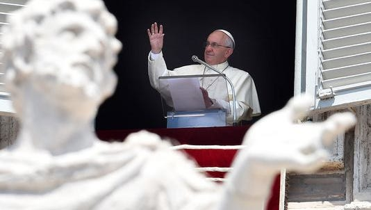 Pope Francis addresses the congregation from the window of the Apostolic Palace overlooking St. Peter's square during his Sunday Angelus prayer at the Vatican on July 19, 2015.