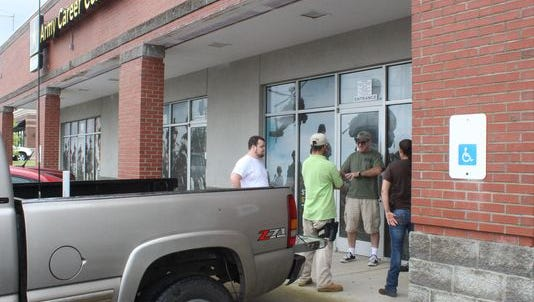Members of a Tennessee Oath Keepers chapter stand outside an Army recruiting center. The Department of Defense asked armed volunteers to stand down on Friday.