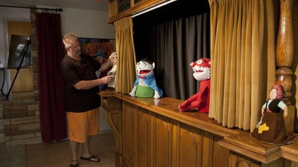 Ernie Doose makes adjustments at the DiFiore Center's puppet theater.