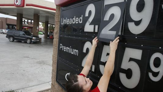 In this file photo, Quick Trip clerk Roxana Valverde adjusts the gas price sign numbers at a QT convenient store as gas prices continue to tumble nationwide in Tolleson, Ariz.