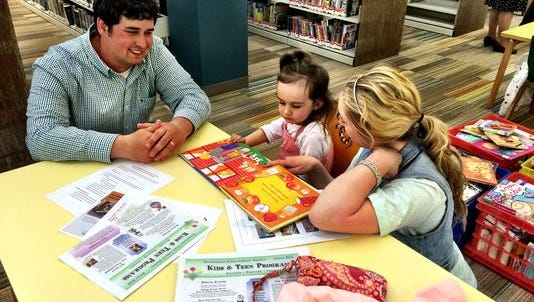 Elliot and Shauna Sheldon and their 2-year-old daughter, Aubree, read books together in the Children's Section during the grand opening of the Boardman Road Branch Library in Poughkeepsie Sunday.