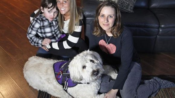 Heather Pereira, right, poses with her daughter, Devyn, left, and Devyn?s nanny, Jenn Horozko, center, with Devyn?s service dog, Hannah.