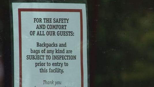 A sign posted outside a Regal theater warns patrons of the chain's bag search policy.