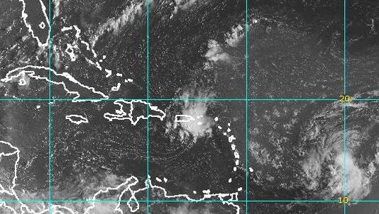 A satellite image taken Tuesday morning shows Tropical Storm Erika (right) spinning east of the Caribbean.