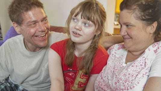 Roger Barbour (left) is shown with daughter Genny and wife Lora. The family, shown several years ago, was in a legal fight to be able to give Genny medical marijuana at school. Roger Barbour is now deceased.