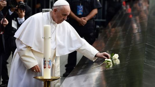 Pope Francis lays a white rose on a memorial at Ground Zero in New York City.