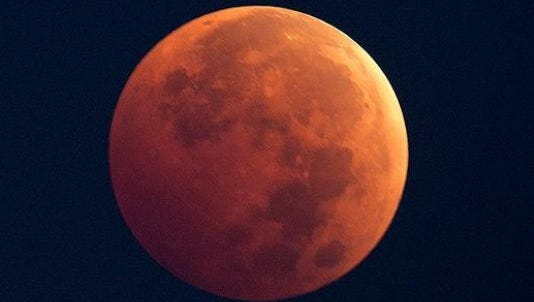"IndyStar photographer Robert Scheer captured this photo of the predawn lunar eclipse, dubbed the ""blood moon"" due to its reddish color."