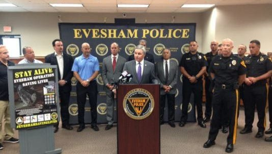 Evesham Mayor Randy Brown (at podium) and Police Chief Christopher Chew (right) are shown at a press conference in August announcing the Evesham Saving Lives program.