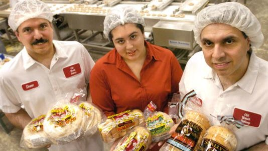 Workers at Skally's Old World Bakery in North College Hill with some of the bakery's pits and bagel products. The company will keep the North College Hill facility but add a new plant in West Harrison, Dearborn County.