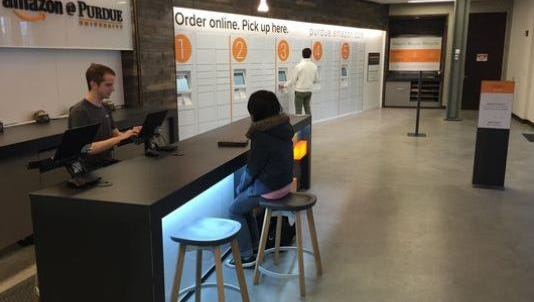 Eric Templin (left), a senior at Purdue University, helps a customers at Amazon's first brick-and-mortar store in Krach Leadership Center.