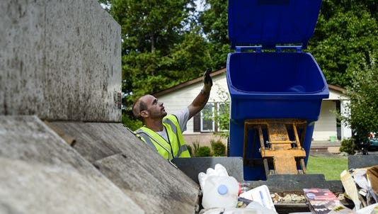 A Curbie worker dumps recyclables into a bin. Recycled materials are sent to end users, not the landfill, the company owner says.