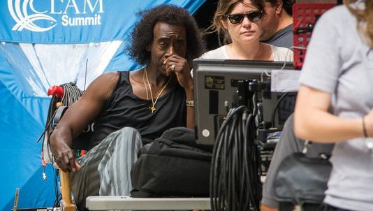 "Star-director Don Cheadle looks at a monitor between shots on ""Miles Ahead,"" his movie about jazz great Miles Davis, on Seventh Street near Elm Street on July 7, the first day of filming."