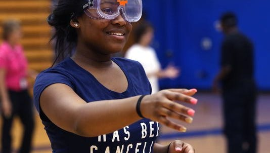 Shortridge High School sophomore Ashauntae Birdsong, wearing a Concussion Goggle that simulates blurred vision resulting from a concussion, tries to make her way across the school's gym as the Dave Duerson Athletic Safety Fund non-profit organization came to the school at 3401 N. Meridian St., Indianapolis, on Monday, Oct. 26, 2015 to heighten concussion awareness among youth.
