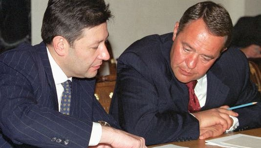 Telecommunication Minister Leonid Reiman, left, and Minister of Press, Television and Radio Broadcasting, Mikhail Lesin, right, confer over documents during a meeting on Aug. 28, 2000.
