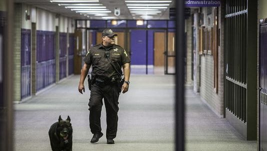 School Resource Officer Dave Williams patrols the hallways at Central High School with his dog, Billy, in September.