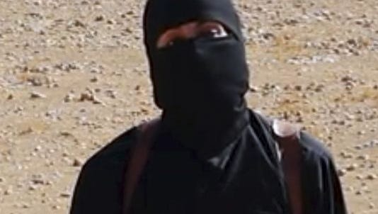 """An undated image shows a frame from a video released Friday, Oct. 13, 2014 by Islamic State militants that purports to show the militant who beheaded taxi driver Alan Henning. A British-accented militant who has appeared in beheading videos released by the Islamic State group in Syria over the past few months bears """"striking similarities"""" to a man who grew up in London, a Muslim lobbying group said Thursday, Feb. 26, 2015. Mohammed Emwazi has been identified by news organizations as the masked militant more commonly known as """"Jihadi John."""""""