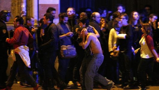 Wounded people are evacuated outside the scene of a hostage situation at the Bataclan concert hall in Paris Nov. 14, 2015.
