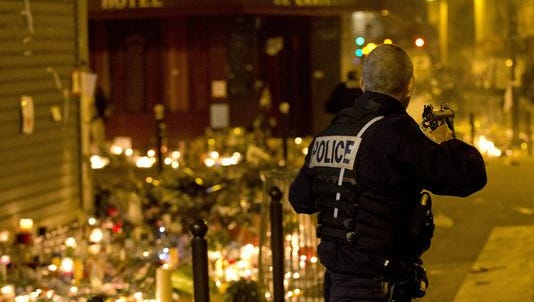 French police secure the perimeter after panic broke out among mourners who payed their respect at the attack sites at restaurant Le Petit Cambodge (Little Cambodia) and the Carillon Hotel in Paris, Sunday, Nov. 15, 2015.