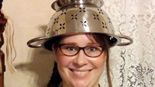 In this Nov. 12, 2015, photo provided by Darrick Fauvel, Lindsay Miller of Lowell, Mass., wears a spaghetti strainer to reflect her religious beliefs while holding her temporary driver's license.