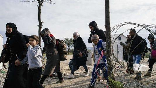 Migrants and refugees cross the Greek-Macedonian border near Gevgelija on Nov. 15.