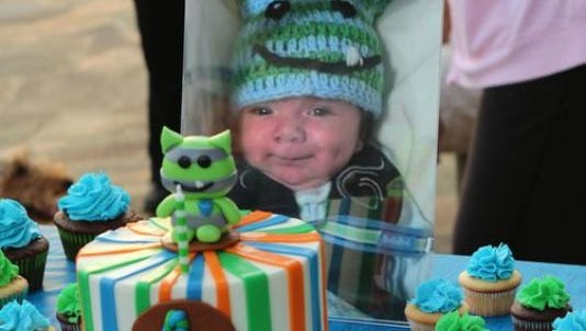 Thomas Castellon II's pictures sits in front of a birthday cake his mother made to celebrate what would have been his first birthday in September 2014. Thomas was killed by a babysitter when he was 2-months old.