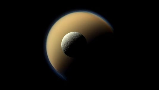 This June 16, 2011 photo provided by NASA/JPL-Caltech/Space Science Institute shows Saturn's largest and second largest moons, Titan and Rhea, appearing to be on top of each other in this true-color scene from NASA's Cassini spacecraft.