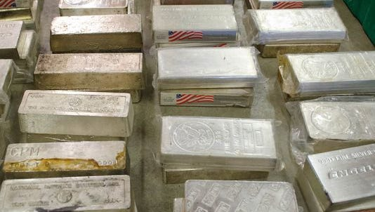 These bars of silver and dozens of firearms, as seen Nov. 20, 2015, were among the items seized during an early Nov. 2015 raid  at a property south of Wheeling, Indiana.