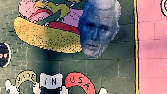 To answer complaints about a mural's depiction of men's genitalia disguised as a hot dog, Paul Baldwin, owner of The Spot, covered part of the mural with a cutout of Gov. Mike Pence's face. The Spot is a the corner of South Fourth and Romig streets in Lafayette.