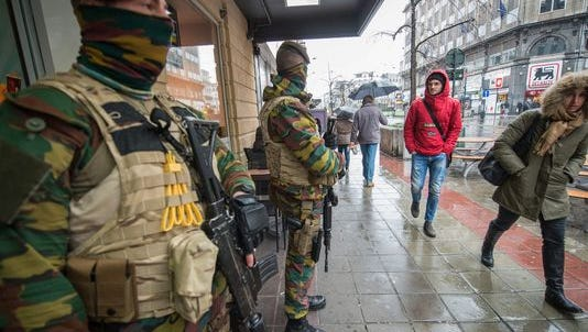 Armed military men stand guard in front of a restaurant in Brussels