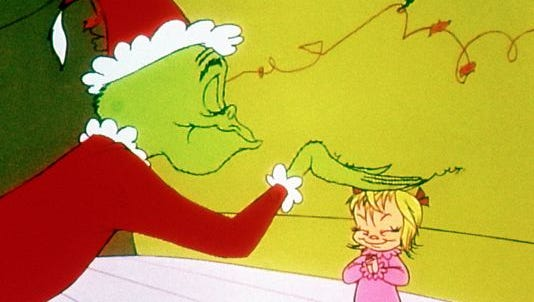 "The Grinch pats little Cindy Lou Who on the head in ""How the Grinch Stole Christmas."""