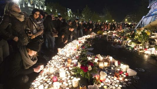 A crowd lights candles at a makeshift memorial in tribute to the victims of Paris' attacks' on Nov. 15 at the place de la Republique in Paris.