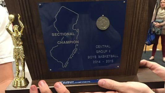 The Manasquan boys basketball players hold the Central Group II trophy from the 2014-2015 season