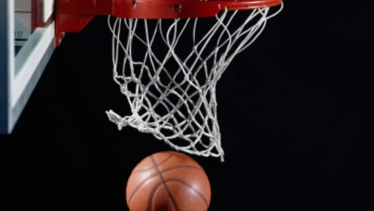 Stock photo of basketball going through hoop.