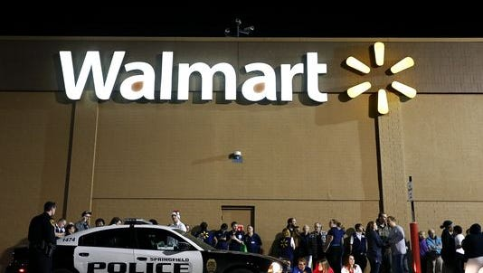 Walmart associates sit under the South Campbell Avenue supermarket's sign in Springfield on Dec. 8, 2015. Police say a man fired a gun inside the store as officers confronted a group over suspected shoplifting.
