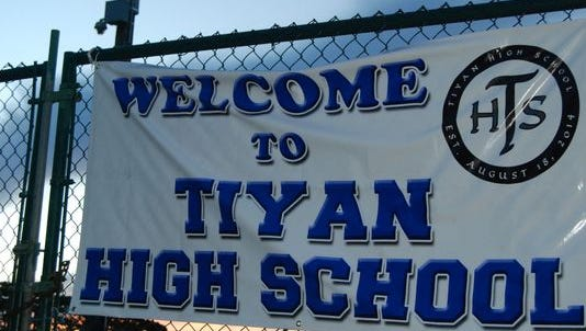 """A """"Welcome to Tiyan High School"""" banner is posted on a fence at the school."""